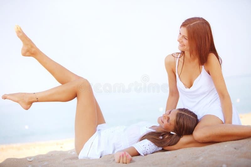 Meninas que descansam na praia foto de stock