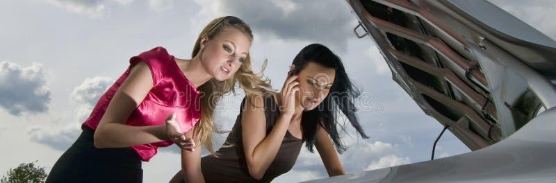 Meninas que estão perto de carro quebrado imagem de stock royalty free