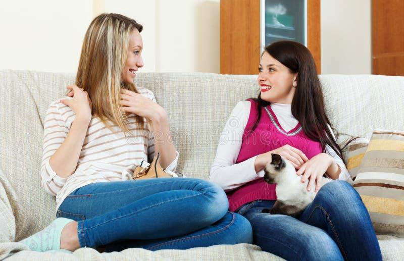 Meninas que falam no sofá imagens de stock royalty free