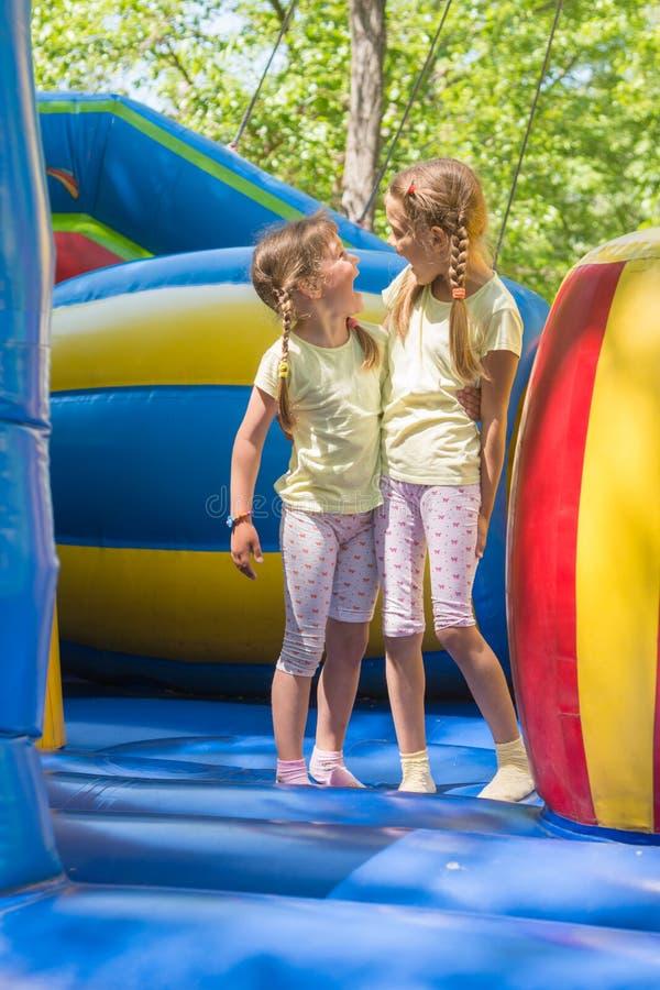 Meninas que fazem caretas felizmente olhando se saltando em um trampolim inflável fotos de stock