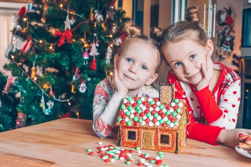 Meninas que fazem a casa de pão-de-espécie do Natal na chaminé na sala de visitas decorada imagem de stock royalty free