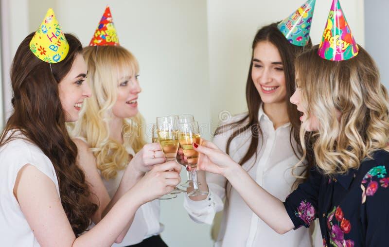 Meninas que felicitam o amigo em seu aniversário com vidros do champanhe à disposição imagens de stock royalty free
