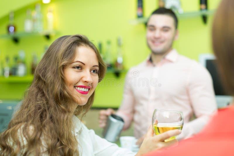 Meninas que flertam com empregado de bar fotografia de stock