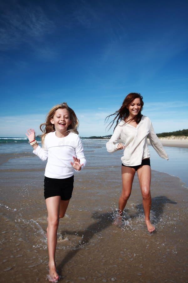 Meninas que funcionam na praia fotografia de stock