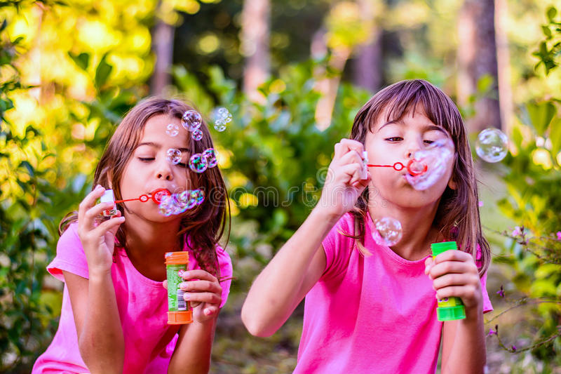 Meninas que fundem bolhas com a varinha no parque fotografia de stock