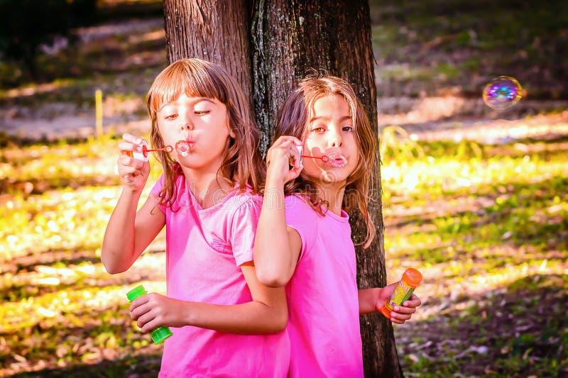 Meninas que fundem bolhas com a varinha no parque imagens de stock royalty free