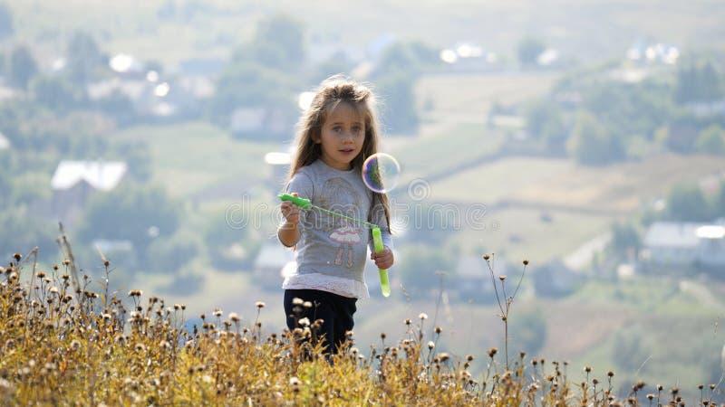 Meninas que fundem bolhas de sabão fotografia de stock