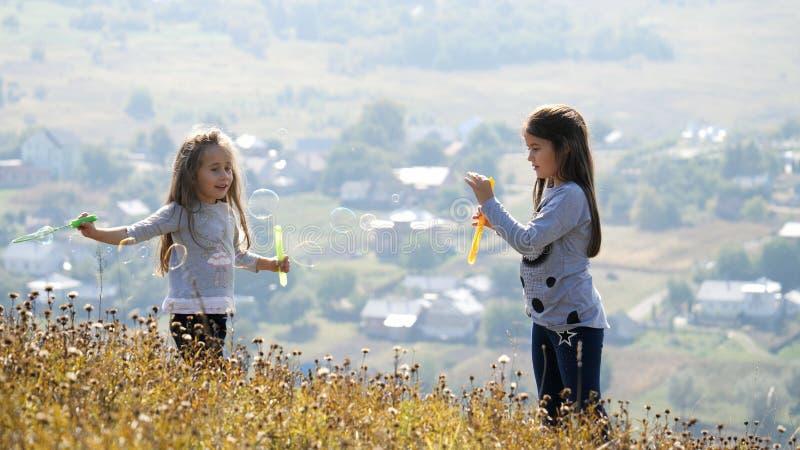 Meninas que fundem bolhas de sabão imagem de stock royalty free