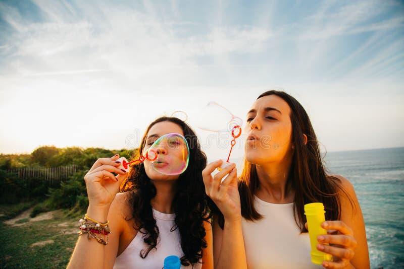 Meninas que fundem bolhas sobre o mar imagens de stock