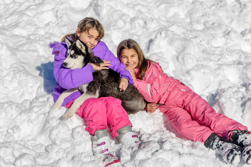 Meninas que jogam com o cão ronco na neve imagens de stock