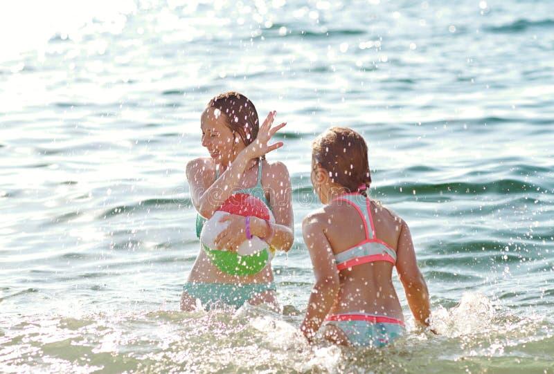 Meninas que jogam no mar foto de stock royalty free