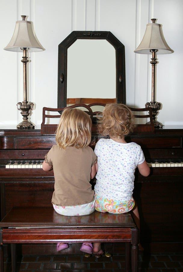 Meninas que jogam o piano imagens de stock