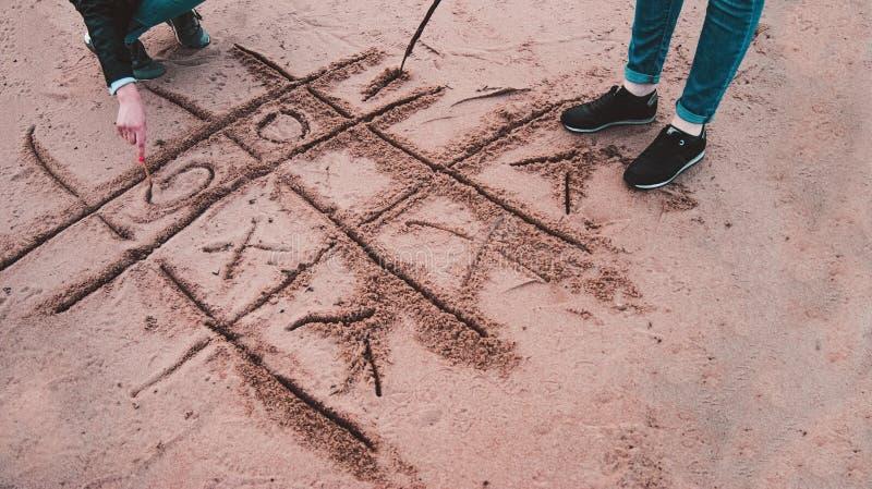 Meninas que jogam o tique-TAC-dedo do pé na praia imagens de stock royalty free