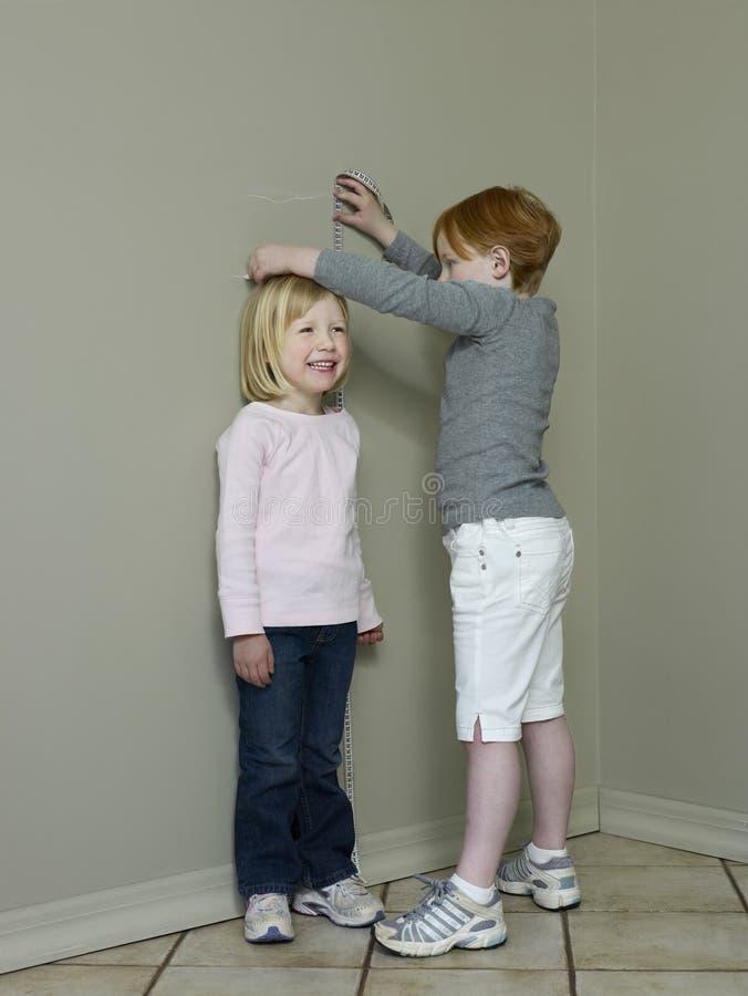 Meninas que medem a diferença da altura contra a parede foto de stock