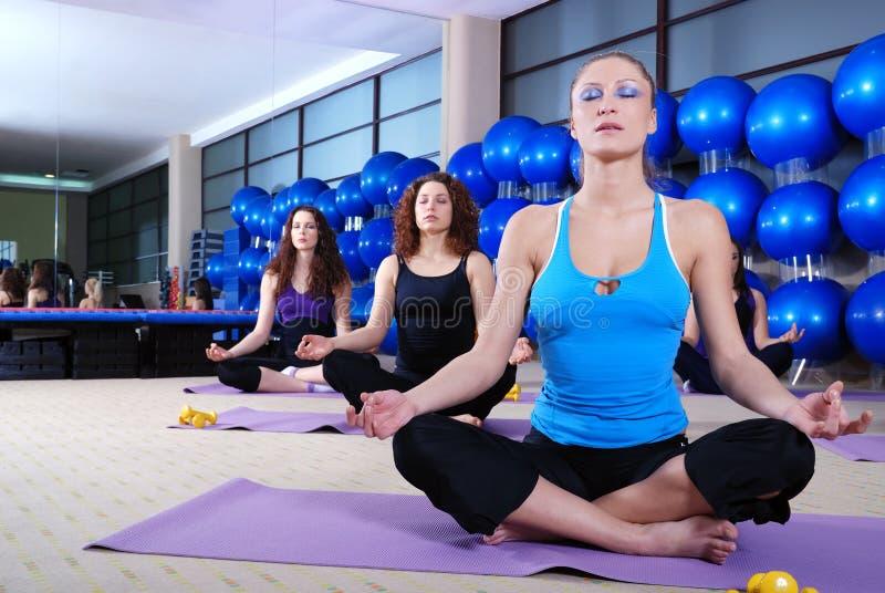 Meninas que meditating no clube de aptidão imagem de stock royalty free