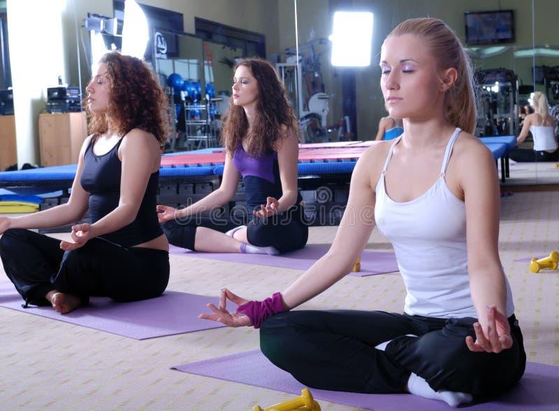 Meninas que meditating no clube de aptidão fotos de stock royalty free