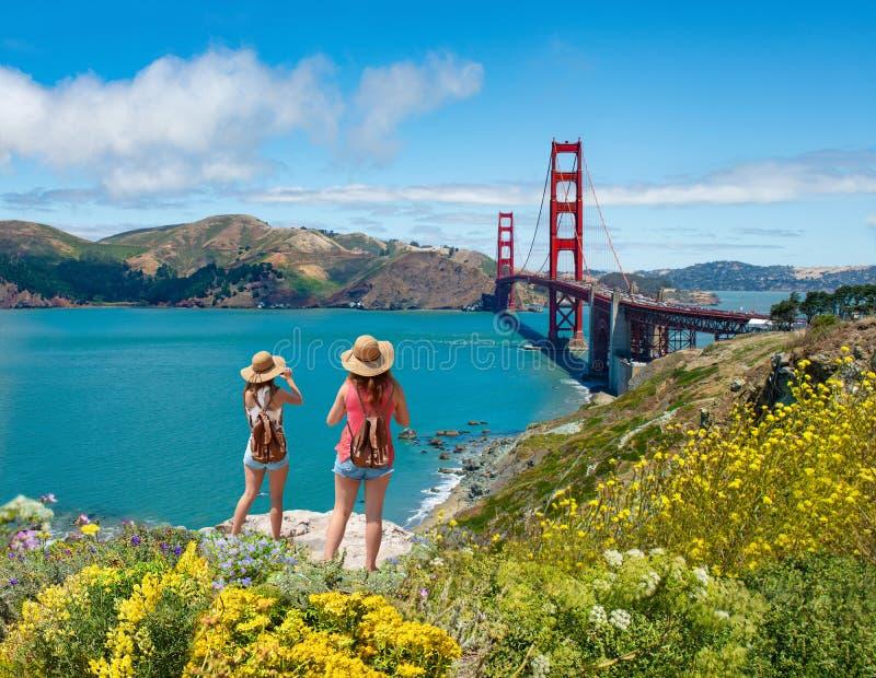 Meninas que olham a vista bonita de golden gate bridge imagem de stock