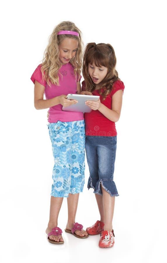 Meninas que prendem o dispositivo da tabuleta fotografia de stock