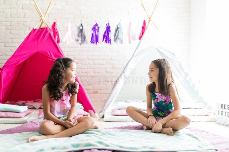 Meninas que sentam-se contra barracas da tenda durante o partido de descanso fotos de stock royalty free