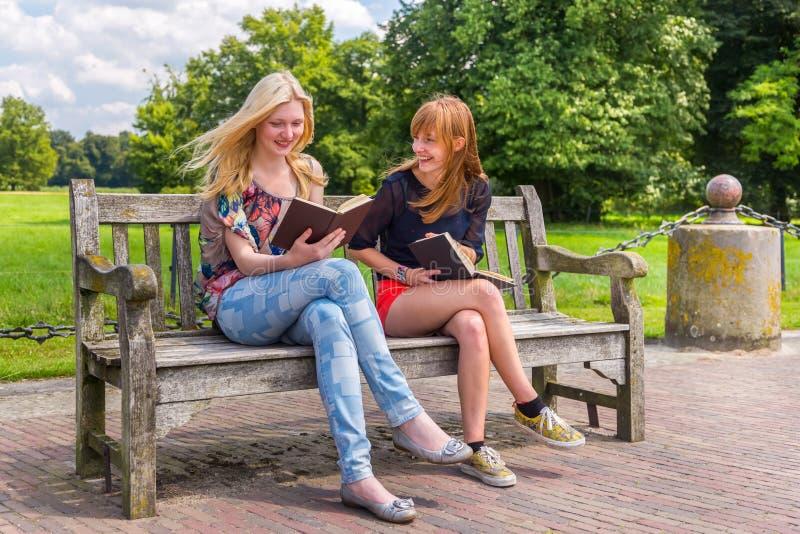 Meninas que sentam-se no banco de madeira em livros de leitura do parque fotografia de stock royalty free