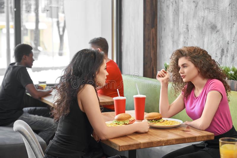 Meninas que sentam-se no café que come o fast food e que comunica-se imagens de stock