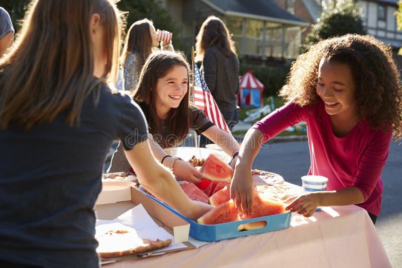 Meninas que servem-se melancia em uma festa do quarteirão fotos de stock royalty free