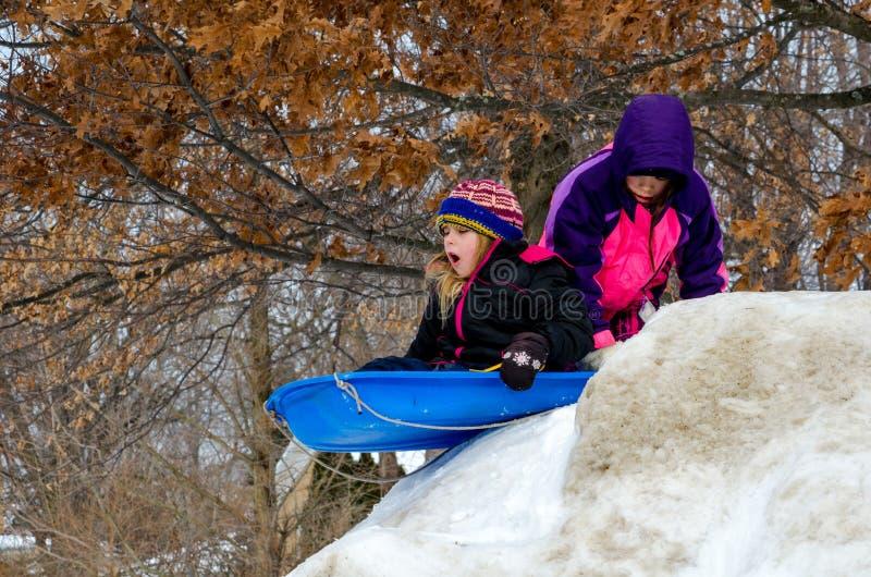 Meninas que sledding em um monte fotografia de stock