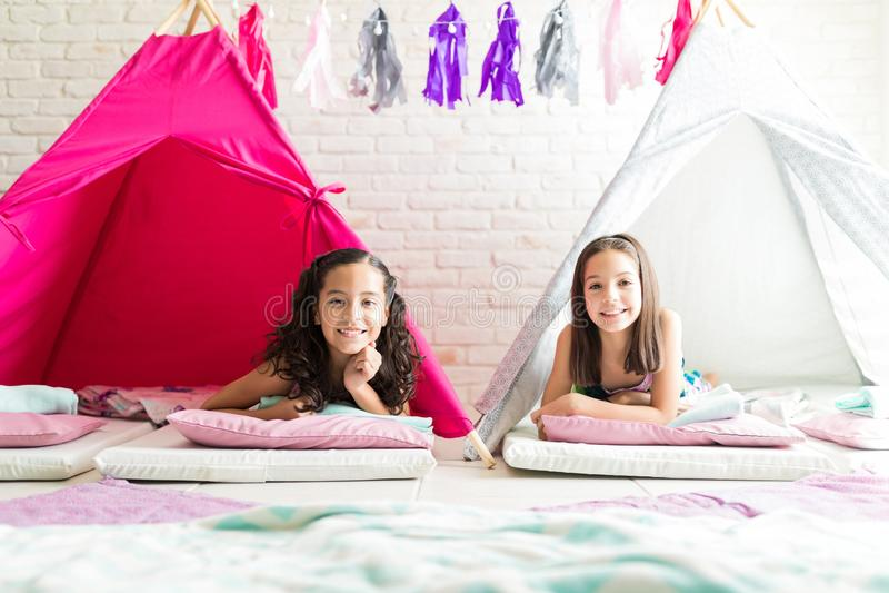 Meninas que sorriem ao descansar em barracas da tenda durante o Sleepover fotografia de stock