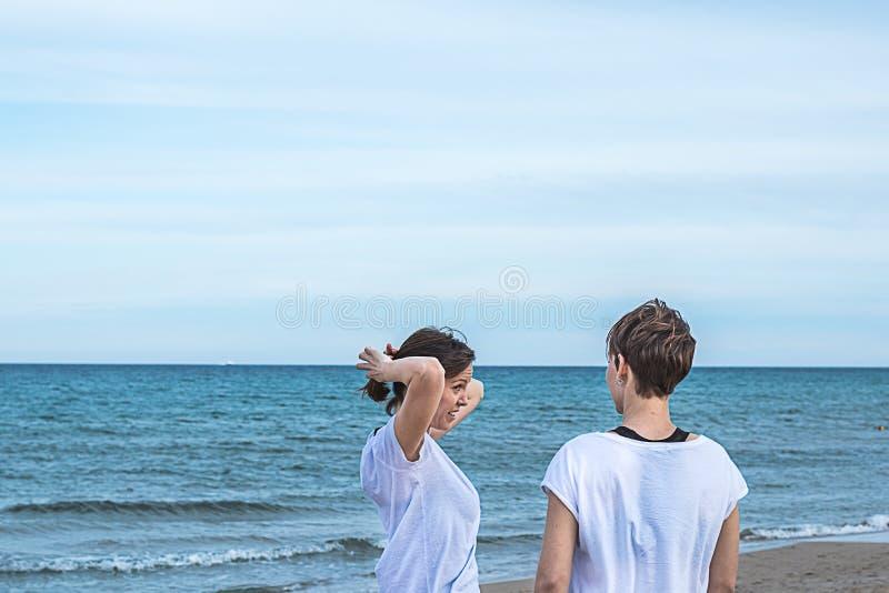 Meninas que sorriem na praia e que puxam sua parte traseira do cabelo com uma atitude normal fotos de stock royalty free