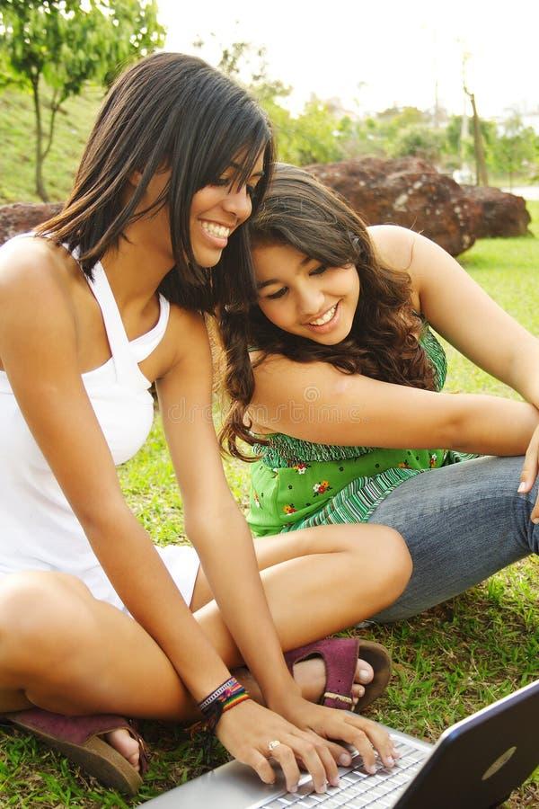Meninas que têm o divertimento com caderno