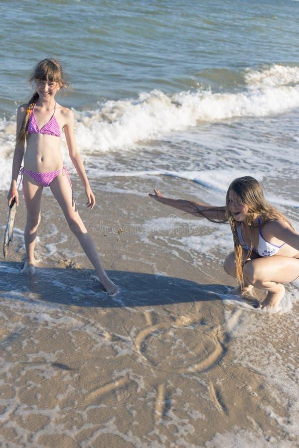 Meninas que tiram na areia na praia no sol do verão foto de stock