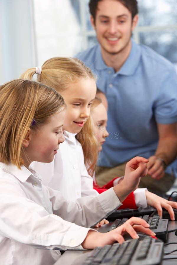 Meninas que usam computadores na classe com professor imagem de stock