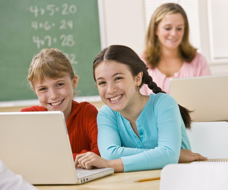 Meninas que usam o portátil na sala de aula