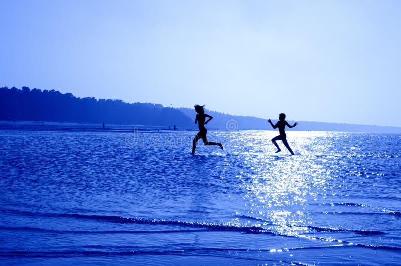 Meninas Running em #2 azul fotos de stock royalty free
