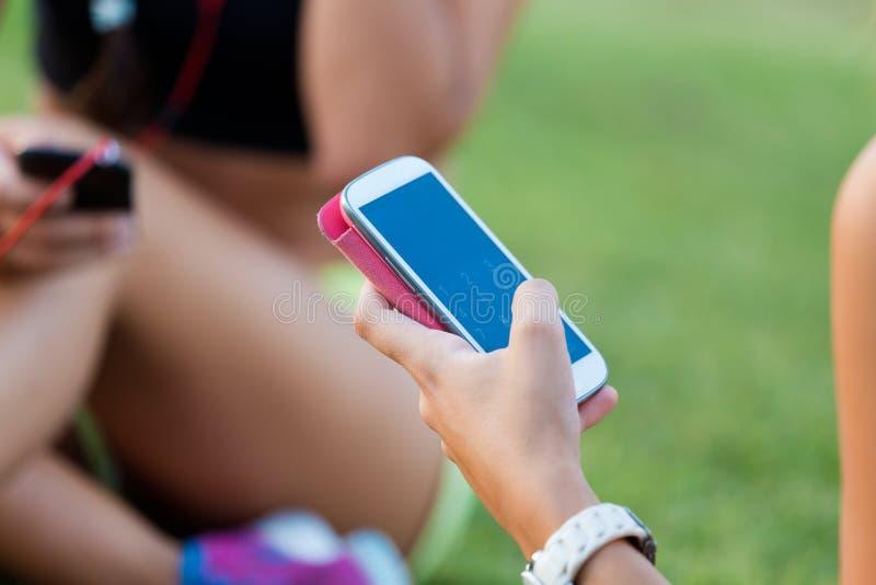 Meninas running que têm o divertimento no parque com telefone celular fotos de stock