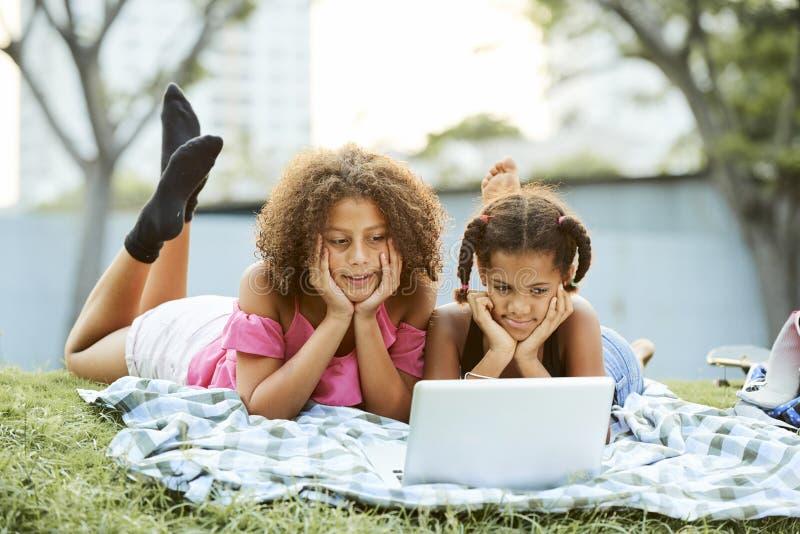 Meninas satisfeitas que olham vídeo interessante no parque imagens de stock
