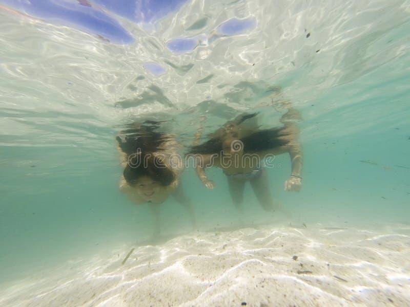 Meninas saudáveis bonitas que nadam debaixo d'água imagem de stock