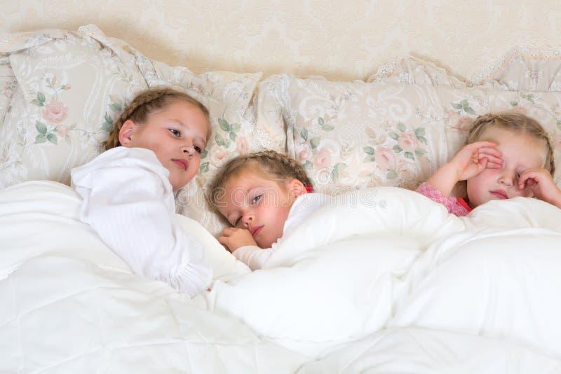 Meninas sonolentos na cama imagens de stock