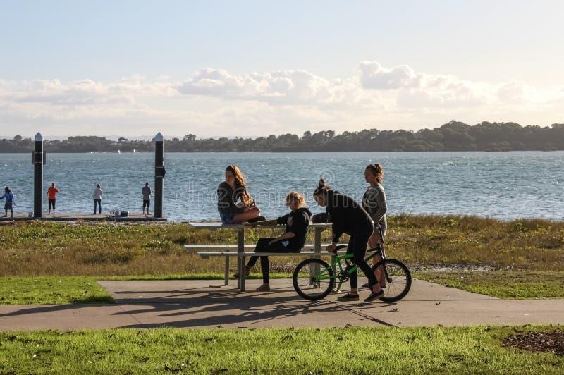 Meninas Teenaged em uma tabela de piquenique para fora pela água num sábado ao fim da tarde Redlands Queensland Austrália no 23 d fotos de stock royalty free