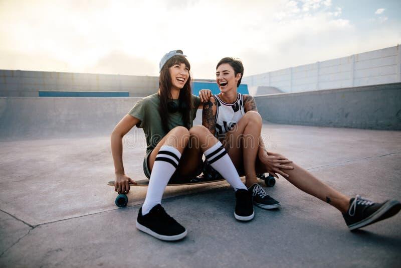 Meninas urbanas que apreciam no parque do patim fotografia de stock royalty free