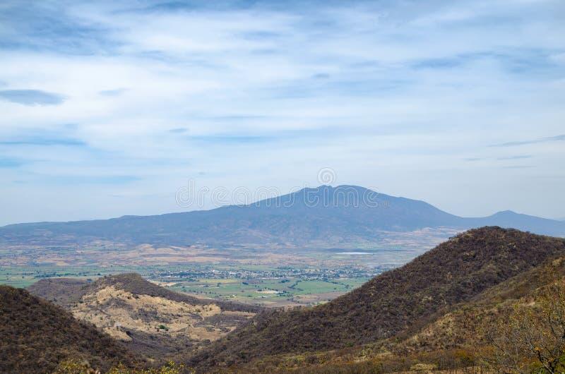 Mening aan de groene vallei, de droge bosheuvels en de bergen bij royalty-vrije stock foto