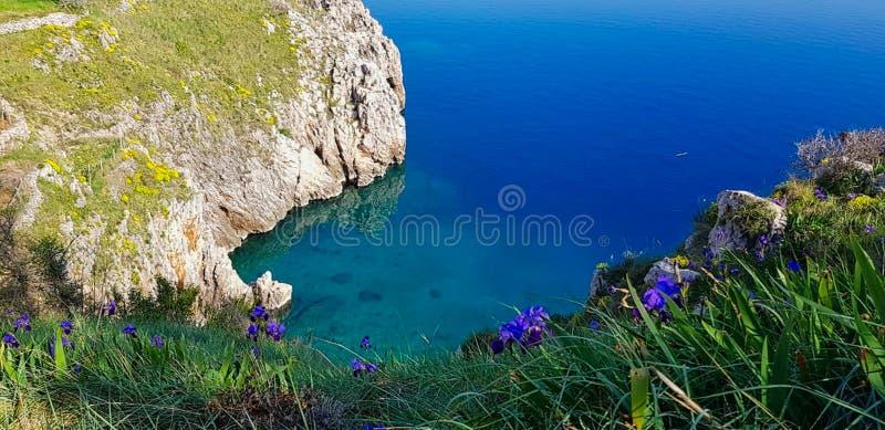 mening aan een klip met blauw water stock foto's