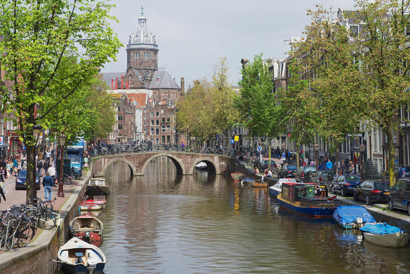 Mening aan het kanaal met de basiliek van Sinterklaas bij de achtergrond in Amsterdam, Nederland royalty-vrije stock foto
