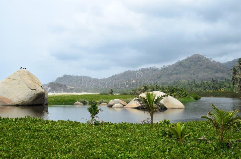 Mening aan lagune en heuvels die met groene tropische vegetatie wordt behandeld stock fotografie