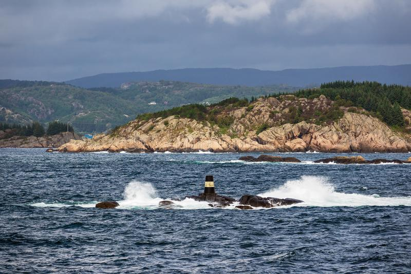 Mening aan Lyngdalsfjord met overzees teken in Noorwegen stock foto's