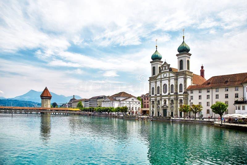 Mening bij de Kapelbrug over Reuss-rivier en Jezuïetkerk in Luzern stock foto