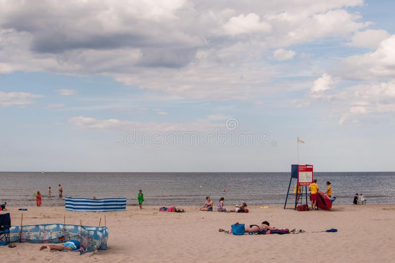 Mening bij het kalme overzees met kleine golven, het hemelhoogtepunt van pluizige wolken en mensen die op het strand op hun handd royalty-vrije stock afbeelding