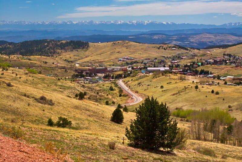 Mening die de stad van Cripple Kreek, Colorado met bergen op achtergrond overzien stock fotografie