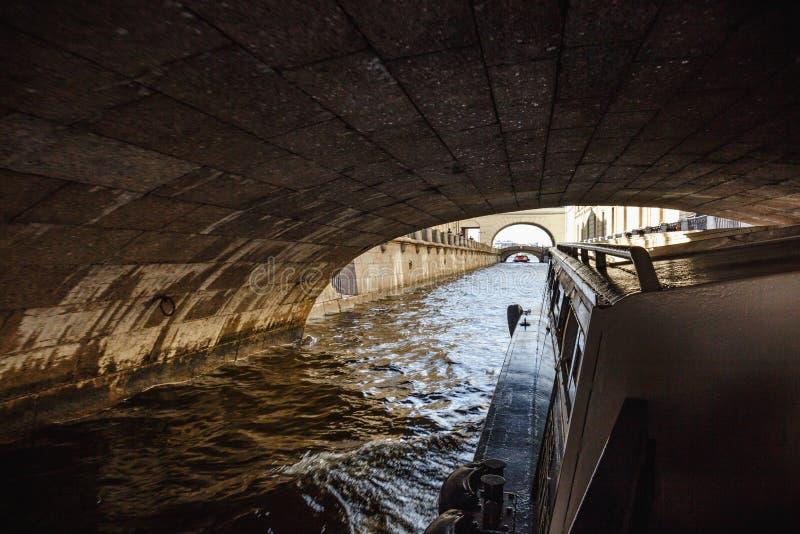 Mening die onder een brug in één van de kanalen of van St. Petersburg door boot drijven royalty-vrije stock foto