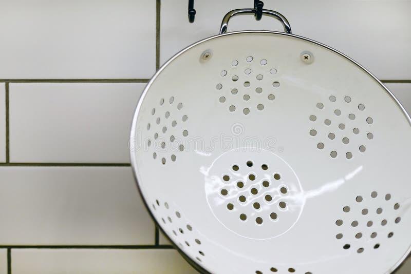 Mening die van de keukenteller met een knipselraad, op de muur verscheidene nuttig, emmers en emmer en schuimspanen hangen stock foto